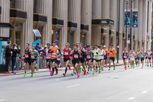 A large group of male athletes running past the Central Standard Building in Chicago