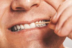 A man cleans his teeth using a wooden toothpick
