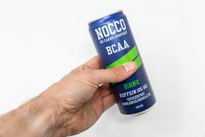 A man holds a can of NOCCO BCAA in the hand on a white background. This fitness drink, here in pear flavour, contains Branched Chain Amino Acid, L-carnitine, caffeine and six different vitamins