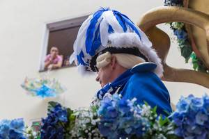 A man in traditional blue-white costume with wig and hat with blue-white feathers. He belongs to the traditional carnival society of the Blaue Funken in Cologne
