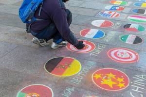 A man places coins on a country flag drawn with chalk on a market place