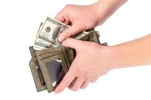 A man puts dollars in an open wallet