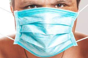 A man with a medical mask on his face close up