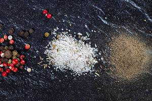 A mixture of peppers, ground black pepper and sea salt on a black background (Flip 2019)