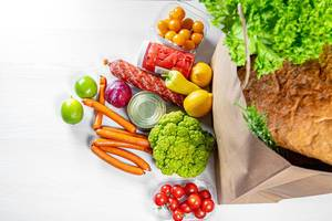 A paper bag full of groceries, surrounded by of fruits, vegetables, sausages and canned goods