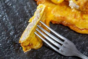 A piece of chops in egg batter on a fork