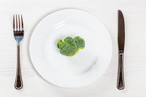 A piece of fresh broccoli on a white plate with a knife and fork. The concept of healthy plant foods