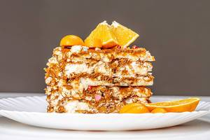 A piece of Kiev cake with condensed milk, nuts and citrus fruits (Flip 2020)