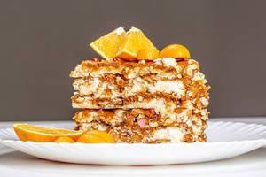 A piece of Kiev cake with condensed milk, nuts and citrus fruits