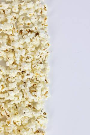 A pile of popping popcorn against a white background