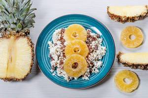 A plate of cottage cheese with flax seeds and dried fruits on a white wooden background with pieces of fresh pineapple (Flip 2019)