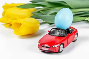 A red car with a blue Easter egg on a white background and a bouquet of yellow tulips