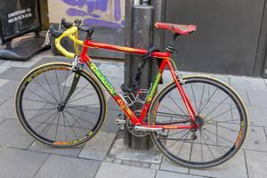 A red Tommasini Racing Bicycle secured to a post