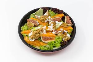 A salat with figs, pumpkin, walnuts and cream cheese in a black bowl