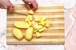 A slices of potatoes on wooden board on marble table
