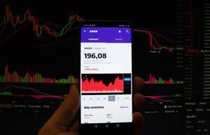 A smartphone displays the Amgen Inc. market value