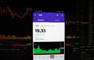 A smartphone displays the CBOE Volatility Index