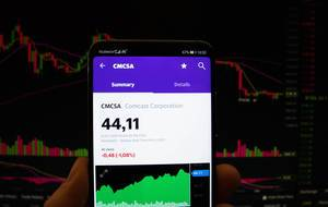 A smartphone displays the Comcast Corporation market value