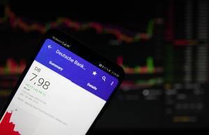 A smartphone displays the Deutsche Bank market value