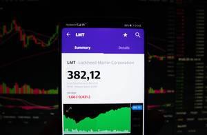 A smartphone displays the Lockhead Martin Corporation market value
