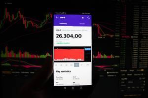 A smartphone displays the Mini Dow Jones market value