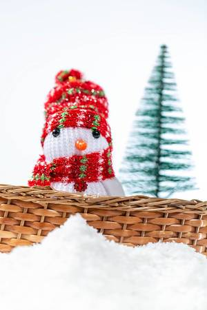 A snowman with hat and scarf inside a basket in the snow with christmas tree in the background