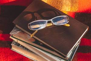 A stack of books and glasses on a blanket. The concept of autumn leisure