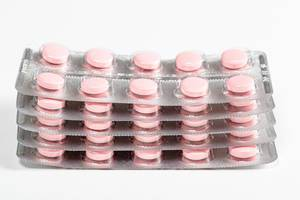 A stack of pink tablets in blisters. Drug treatment concept
