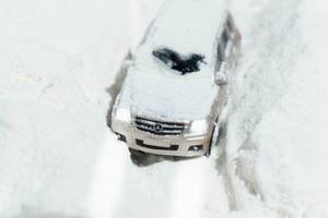 A terrain car is driving on a dirt road covered in snow