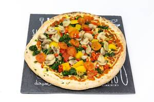 A vegan pizza with mushrooms, peppers, spinach and cherry tomatoes