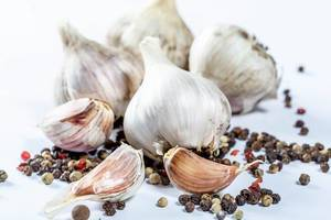 A whole head of garlic and cloves with a tooth of pepper peas on a white background