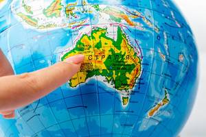 A woman points to Australia with her finger on a globe