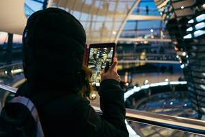A woman taking picture inside Reichstag Dome with a tablet