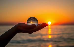 Abenddämmerung und Horizont spiegelt sich mit dem Meer in einem Glasball