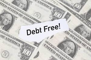 """Abgerissener Notizzettel mit dem Text """"Debt Free!"""" (Schuldenfrei) auf amerikanischen einhundert Dollar-Scheinen"""