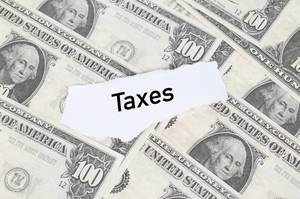 """Abgerissener Notizzettel mit dem Wort """"Taxes"""" (Steuern) auf amerikanischen Dollarscheinen"""