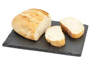 Abgeschnittenes Weißbrot mit zwei Brotscheiben auf einer Schiefersteinplatte