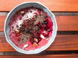Acai bowl with chocolate, berries, almonds and coconut