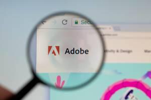 Adobe-Logo am PC-Monitor, durch eine Lupe fotografiert