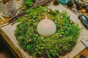 Adventskranz Arrangement mit einer runden Kerze in der Mitte