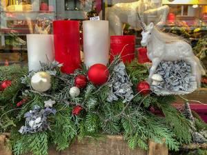 Adventskranz aus Tannenzweigen mit roten und weißen Kerzen, Weihnachtskugeln und Sternen und einem glitzernden Einhorn