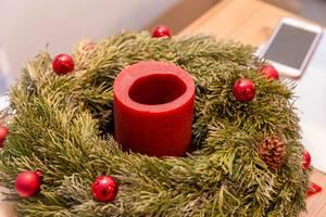 Adventskranz mit einer, teilweise abgebrannten, Kerze und roten Weihnachtskugeln vor Smartphone