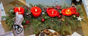 Adventskranz mit vier angezündeten Kerzen sowie Geschenke und Weihnachtskekse
