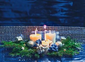 Adventskranz mit weißen Kerzen, silbernen Kugeln und netz auf blauem Hintergrund