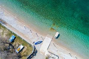 Aerial drone shot of a pebble beach with turquoise water in the winter time