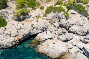 Aerial photo shows tourists on a rocky coast, exploring the sights Bekiris Cave on the Saronic island Spetses