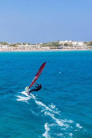 Aerial photography of a fast windsurfing water sports enthusiast in front of Santa Maria Beach of Paros, Greece, in the Mediterranean Sea