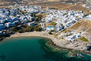 Aerial photography of Naoussa in Greece, with white limestone houses, Piperi Beach and the green Mediterranean Sea