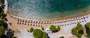 Aerial photography of tourists relaxing on vacation & swimming in the green sea at Plaza Paraskevi beach in Agii Anargiri, Spetses
