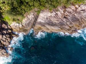 Aerial picture shows waves of the deep blue ocean in front of the cliffs of Ros Lepa in Mahé, Seychelles